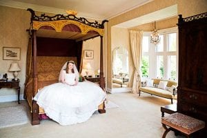 Bride sitting on a four poster bed
