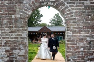 Bride and groom walking through a stone arch