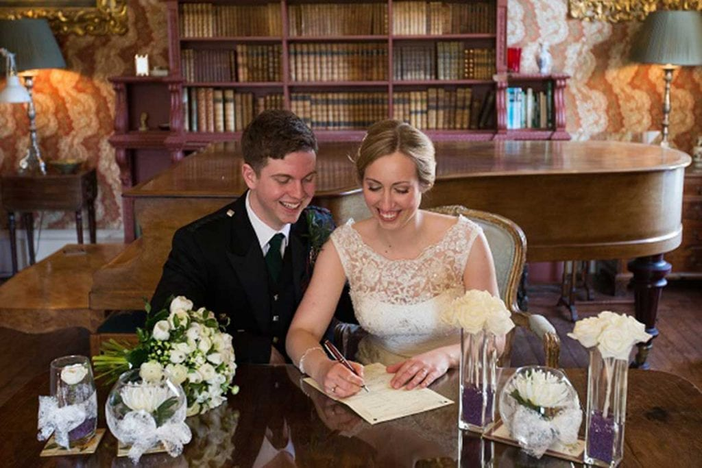 Wedding couple signing a book
